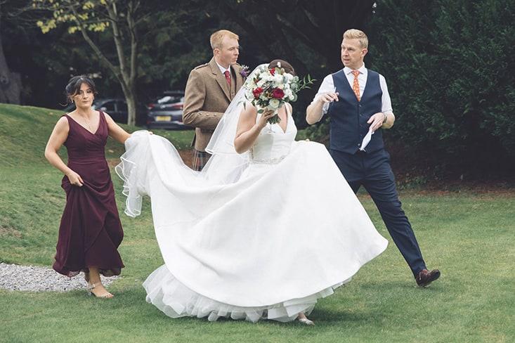 Wedding Photographer straightening brides dress for photographs